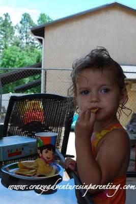 toddler eating chips on dora plate
