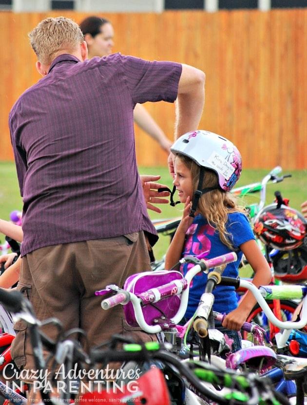 dad helping her with her helmet