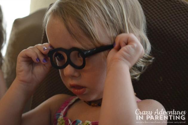 trying on Mr. Potato Head's glasses