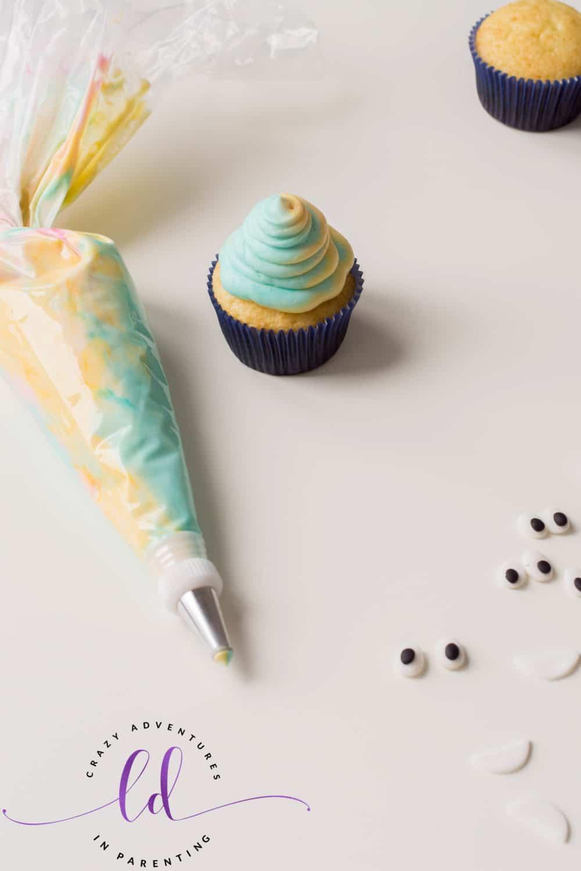 Pipe frosting onto Tie-Dye Poop Emoji Cupcakes
