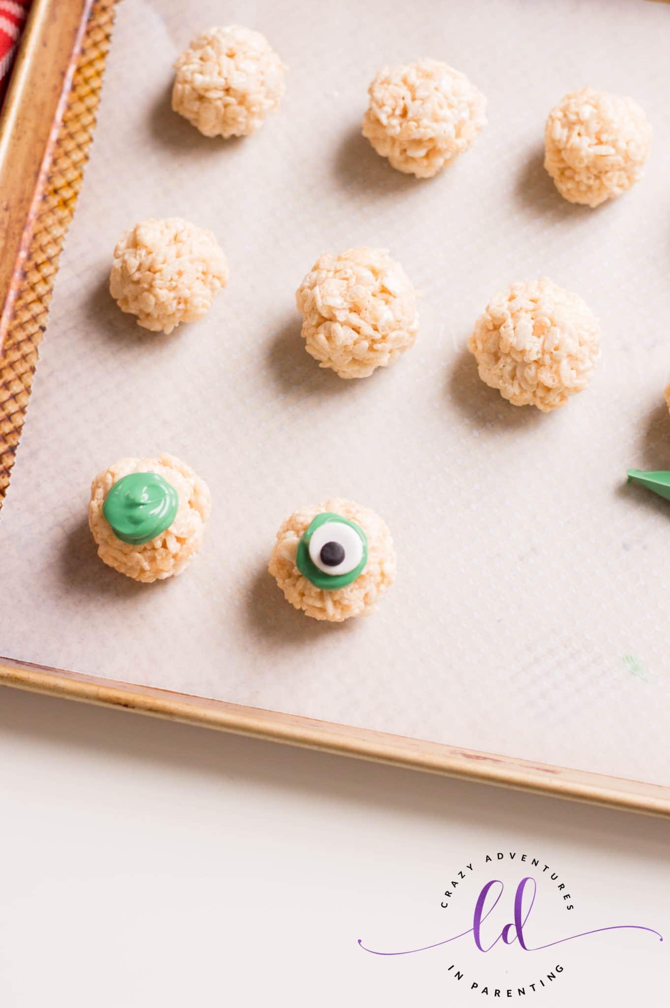 Pipe Green Candy onto Eyeball to Make Halloween Eyeballs Rice Krispies Treats